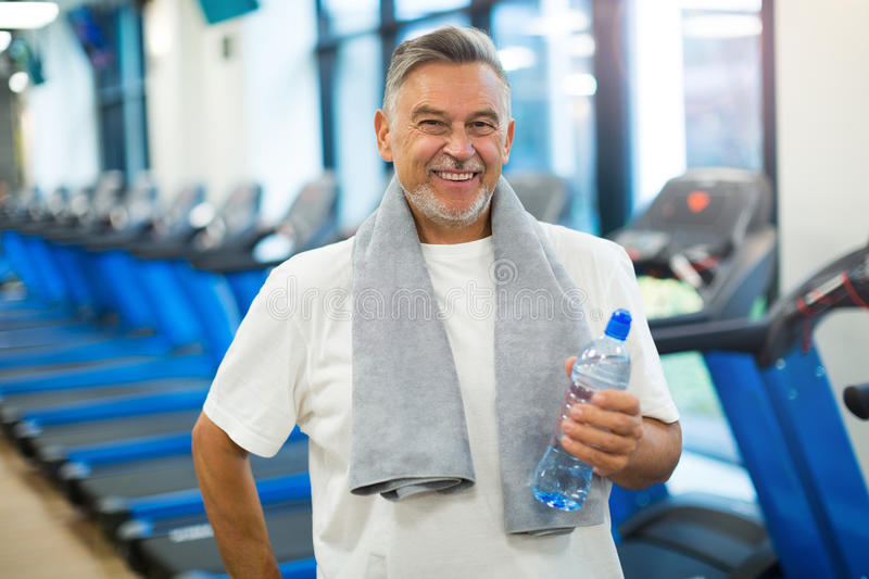 Mature man in health club. Mature man doing fitness exercises royalty free stock photography