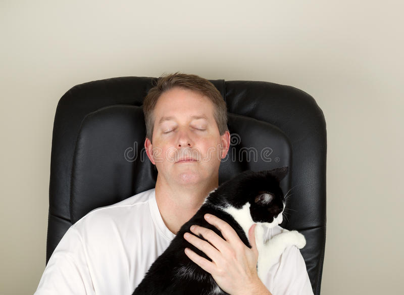 Mature Man and his cat relaxing in massage chair stock photo