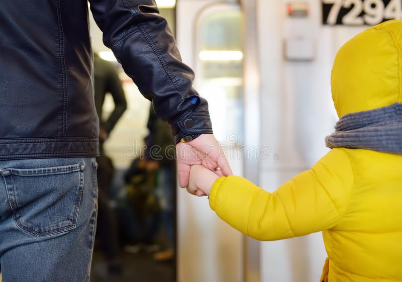 Mature man and his little son looks out the window of the car in the subway in new York stock photography