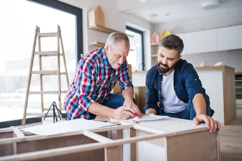 A mature man with his senior father assembling furniture, a new home concept. stock photo