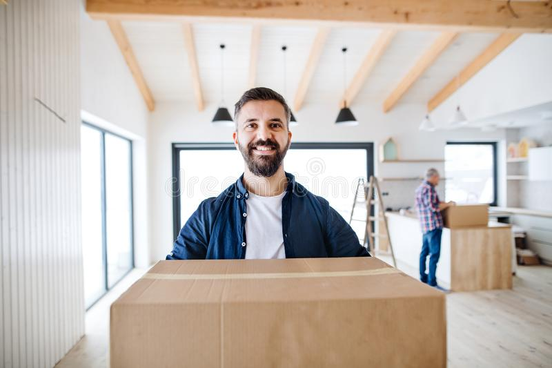 A mature man with his senior father furnishing new house, a new home concept. royalty free stock images