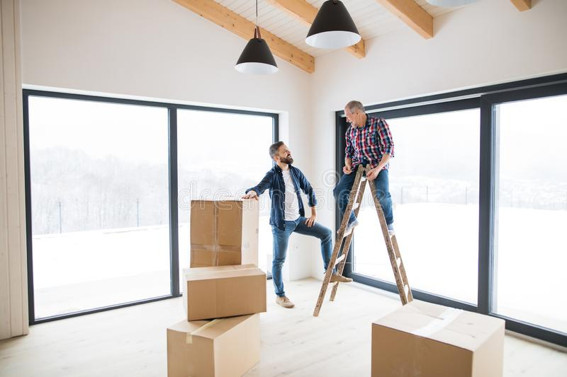 A mature man with his senior father furnishing new house, a new home concept. royalty free stock photography