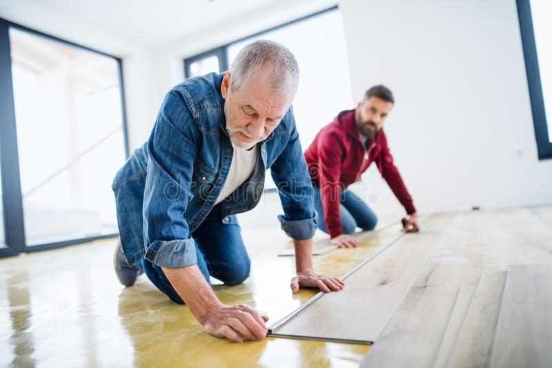 A mature man with his senior father laying vinyl flooring, a new home concept. royalty free stock photography