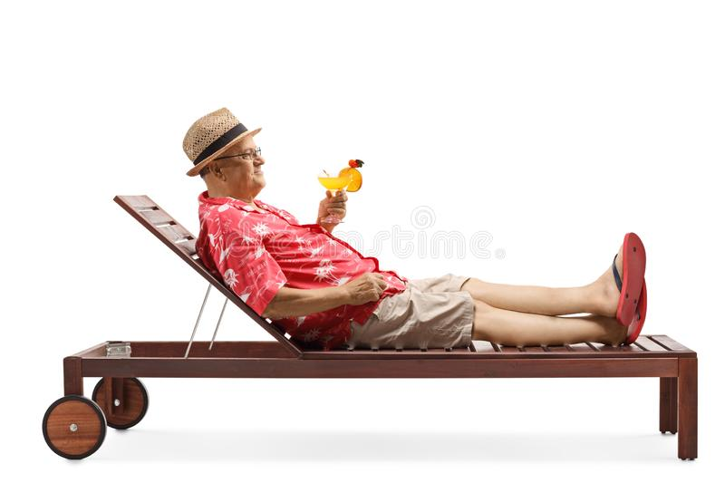 Mature man holding a cocktail and relaxing on beach bed stock images