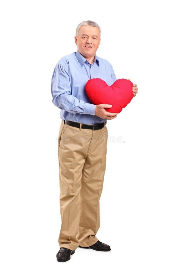 Mature man holding a red heart shaped pillow