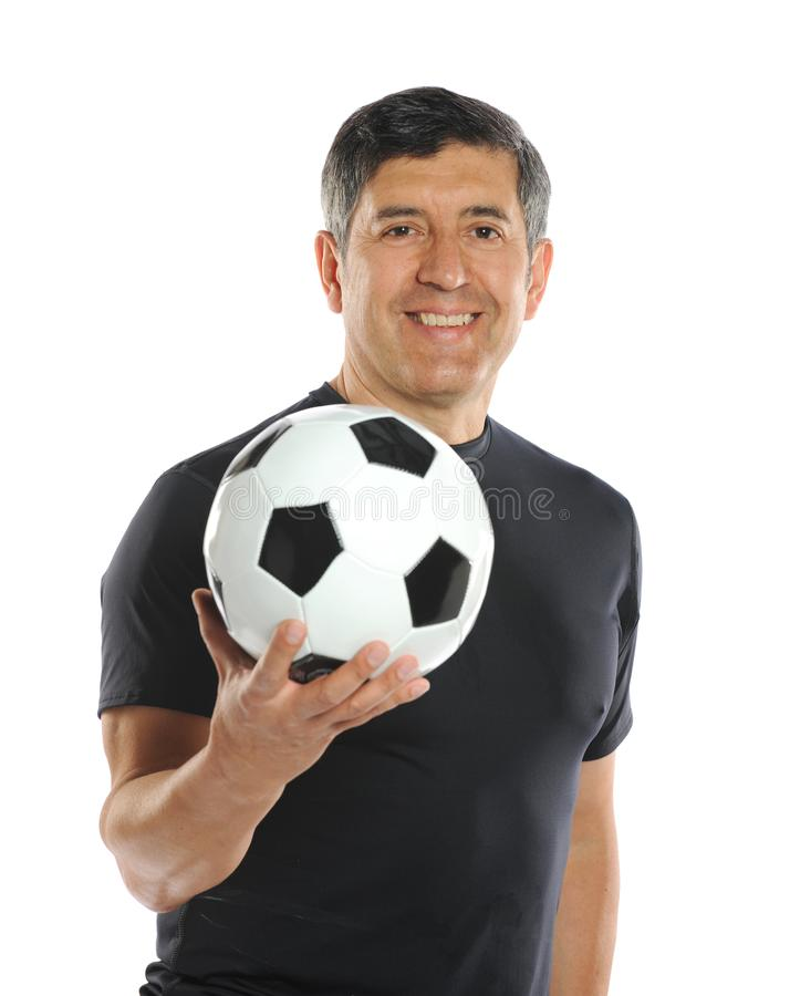 Mature man holding a soccer ball. Isolated on a white background royalty free stock photo