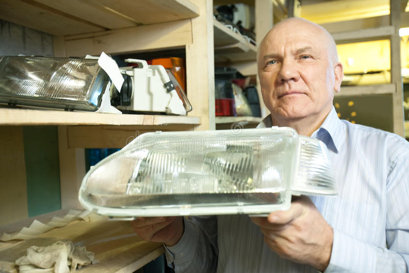 Mature man holds  automotive  headlight