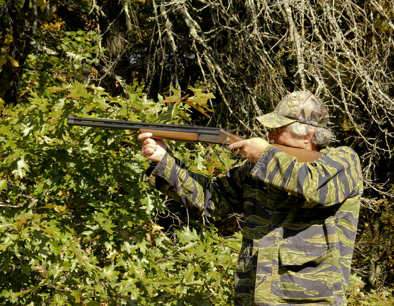 Mature man hunting. With a shotgun with a woods and forest background royalty free stock photography