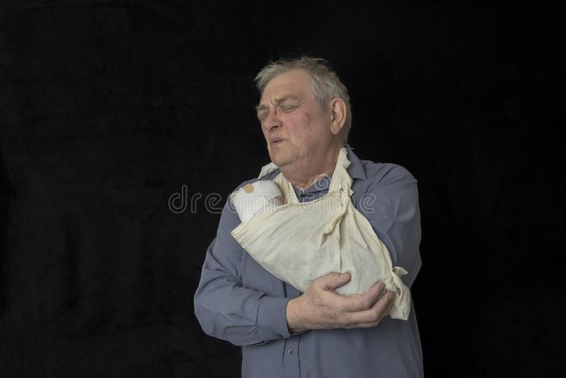 Mature man with injured arm in a sling stock images