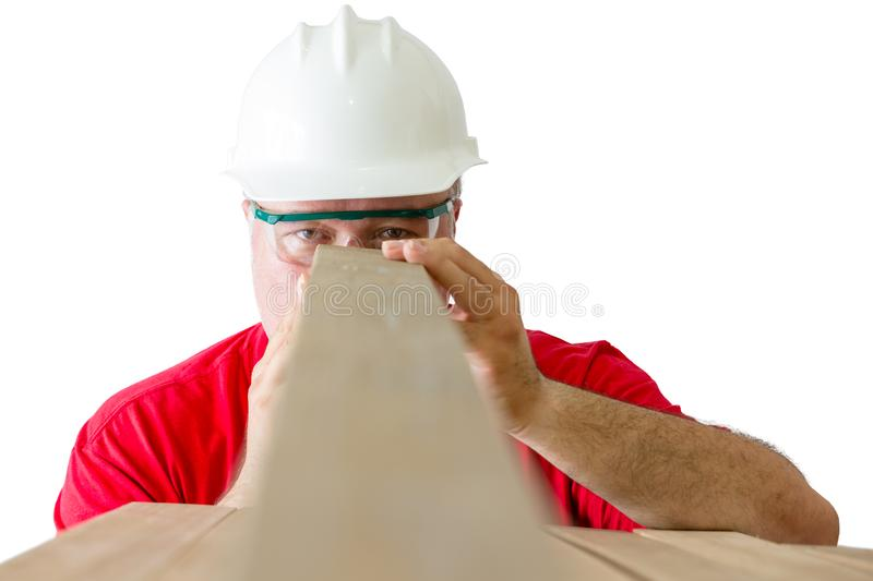 Mature man inspecting quality of wooden plank stock photo