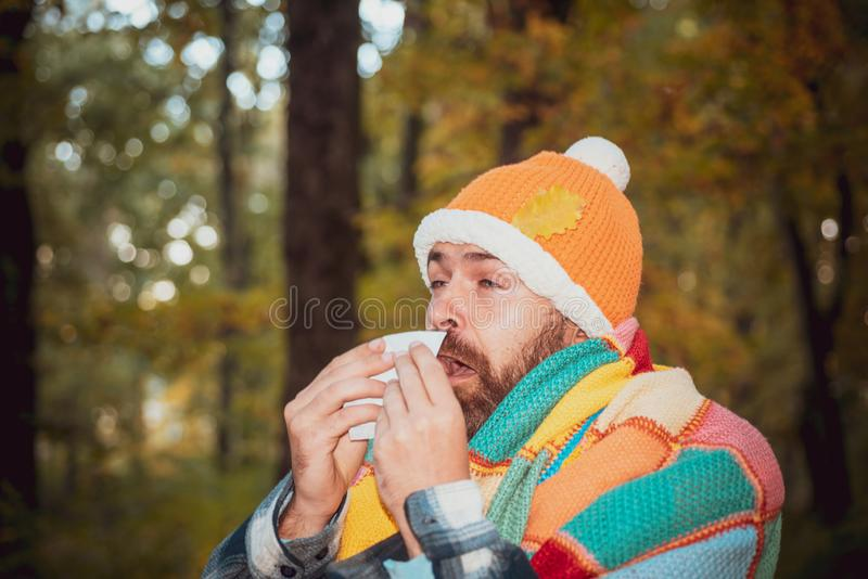 Mature man in jacket suffering from cold. Blowing nose with a tissue, looking miserable unwell very sick. Healthcare and stock photos