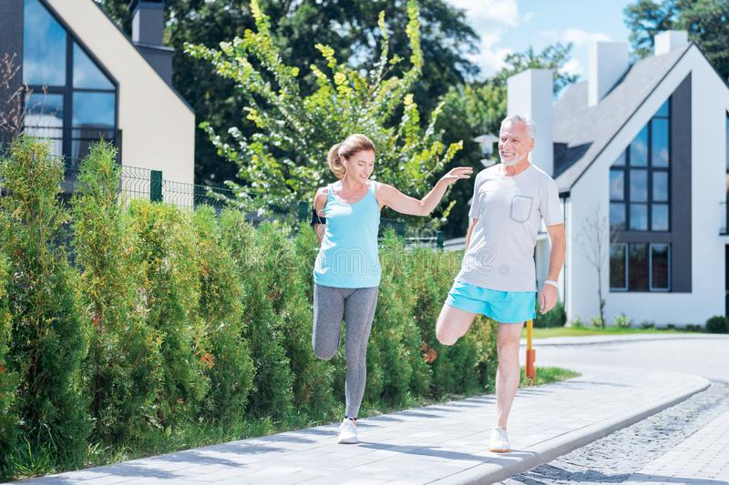 Mature man joining his beautiful slim woman while running in the morning royalty free stock photography