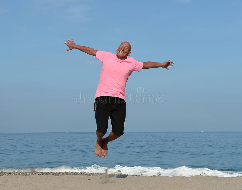 Mature man jumping on beach royalty free stock photo