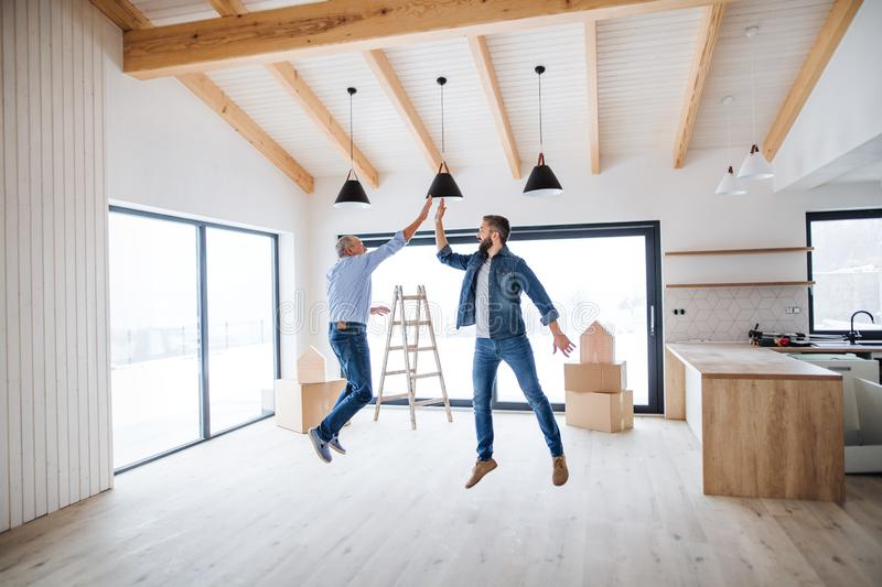 A mature man jumping with his senior father in new house, a new home concept. stock images