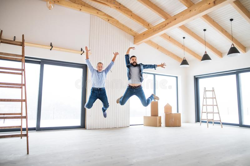 A mature man jumping with his senior father in new house, a new home concept. stock photo
