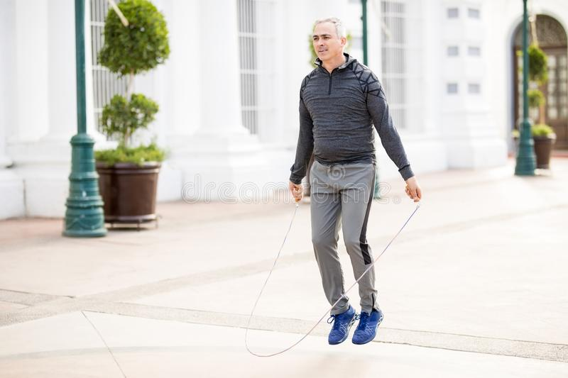 Mature man jumping a rope and exercising outdoors. Good looking middle aged man jumping a rope and exercising outdoors in the city royalty free stock images