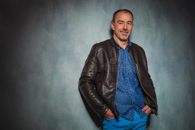 Mature man in leather jacket standing in gray studio stock images