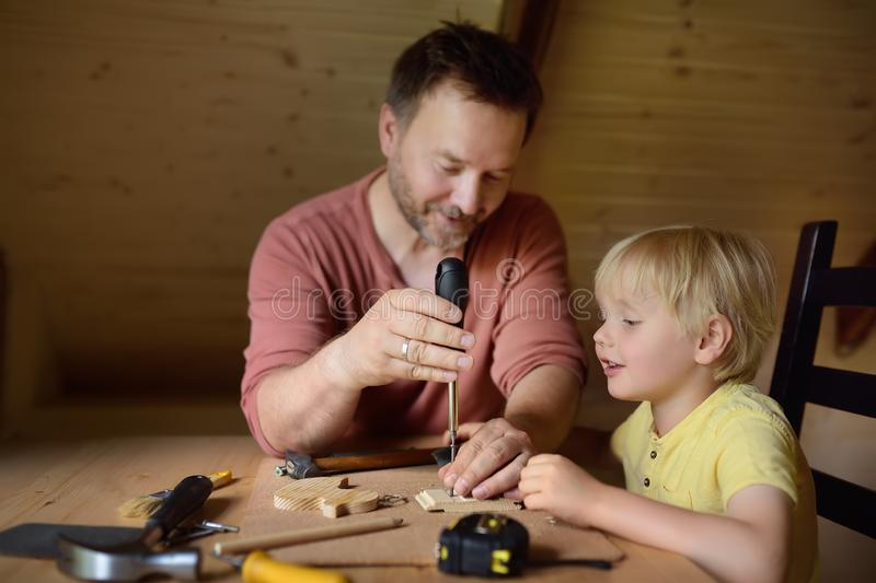 Mature man and little boy make a wooden toy together. Father learn his son work with tools.Traditional education of boy. Family`s royalty free stock photography
