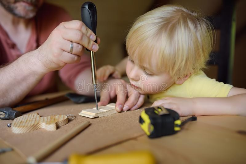 Mature man and little boy make a wooden toy together. Father learn his son work with tools.Traditional education of boy. Family`s. Mature men and little boy make royalty free stock photos