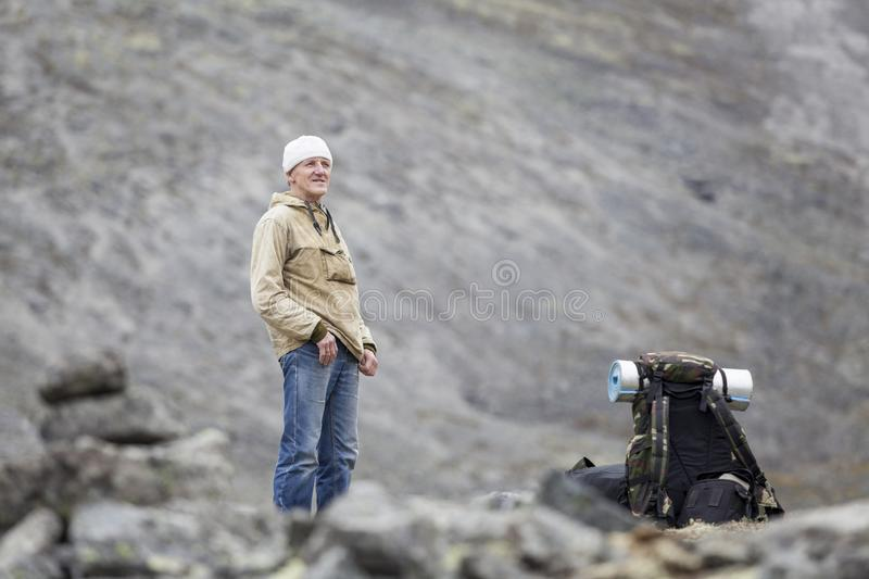 Mature man looking around while standing on passage and resting without backpack royalty free stock images