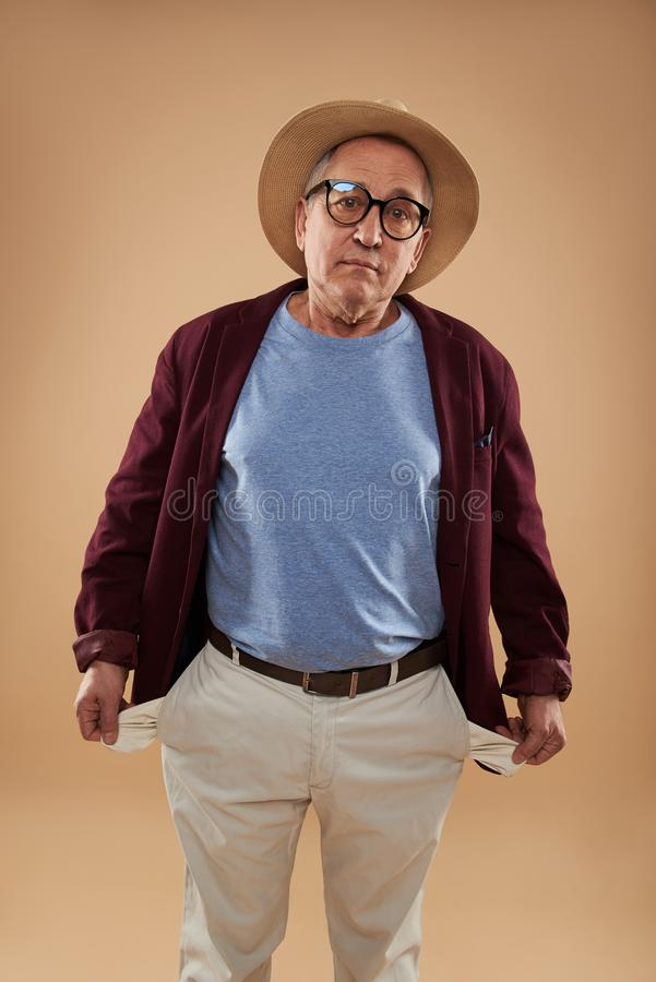 Mature man looking upset and showing his empty pockets royalty free stock image