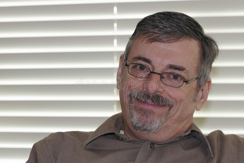 Mature Man Looking at Viewer. An attractive older man wearing eyeglasses, graying goatee, and brown shirt looks at the viewer with a tilted head, and closed royalty free stock photo