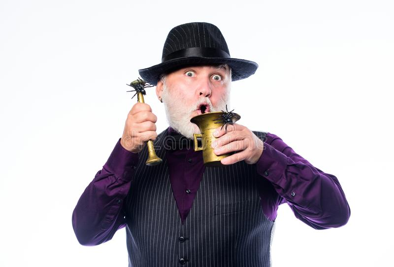 Mature man magician in witch hat. happy halloween. barman make cocktail for halloween party. evil wizard cooking magic. Potion with spider. halloween holiday stock photography