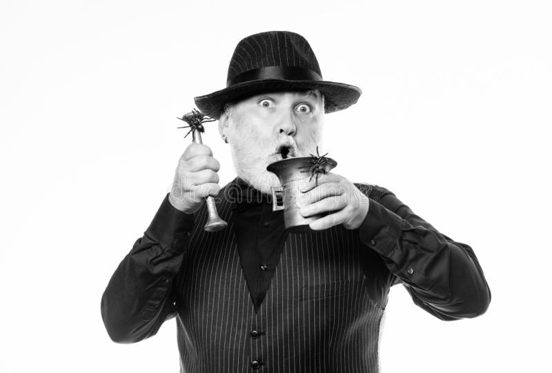 Mature man magician in witch hat. happy halloween. barman make cocktail for halloween party. evil wizard cooking magic royalty free stock photos
