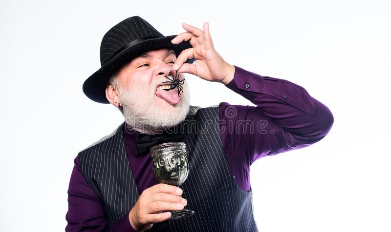Mature man magician in witch hat. happy halloween. evil wizard cooking magic potion with spider. barman make cocktail royalty free stock image