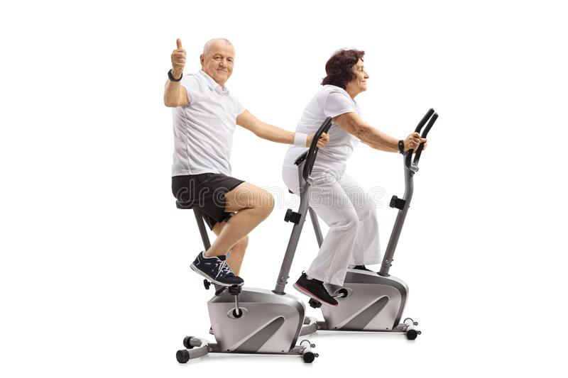 Mature man and a mature woman on exercise bikes with the man making a thumb up sign royalty free stock photography