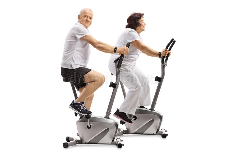 Mature man and a mature woman exercising on stationary bikes royalty free stock image
