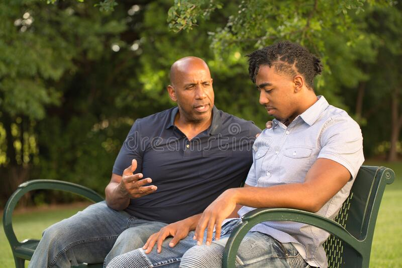 Mature man mentoring and giving advice to a younger man. Father mentoring and giving advice to a younger man stock photo