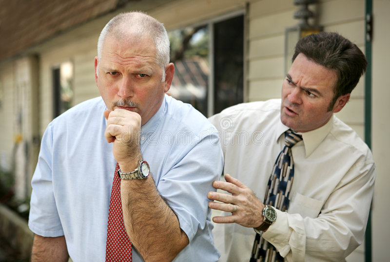 Mature Man - Pat on Back. A mature businessman with a severe cough. His worried colleague is patting him on the back. Focus on coughing man stock image