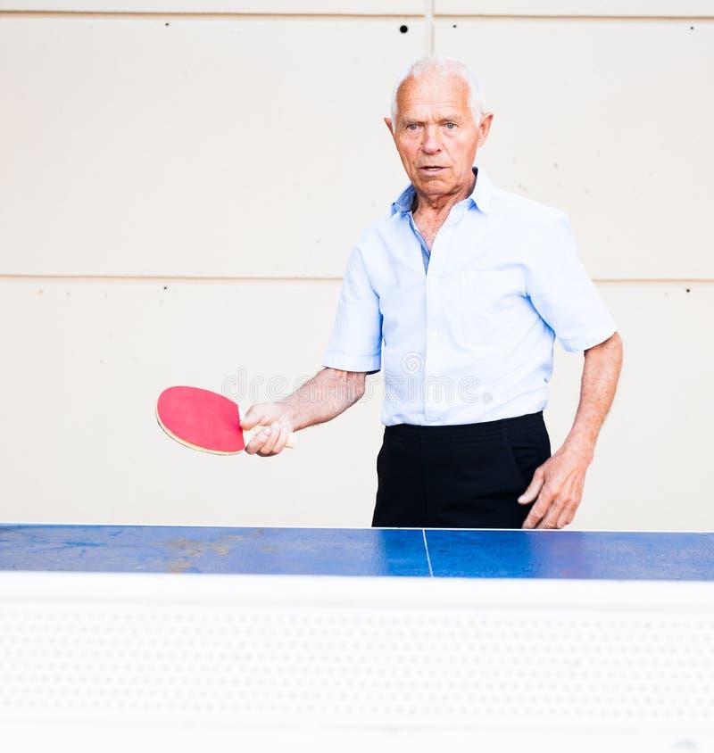 Mature man playing ping pong outdoors. Ordinary mature man playing ping pong outdoors royalty free stock photos
