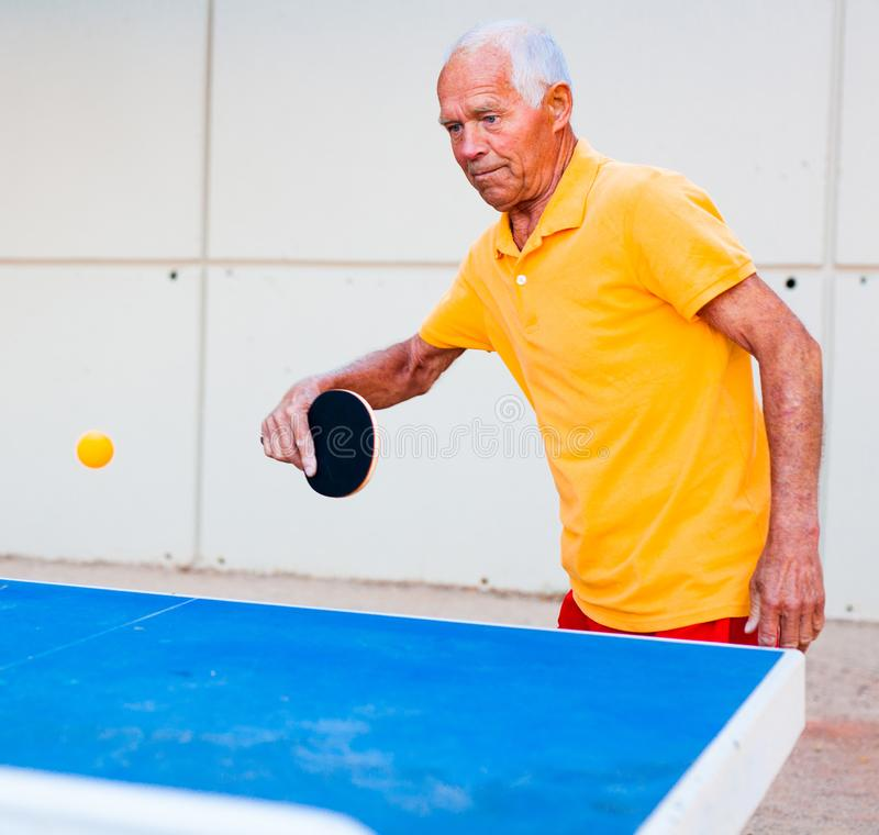 Mature man playing ping pong outdoors. Mature man in yellow Tshirt playing ping pong outdoors royalty free stock photography