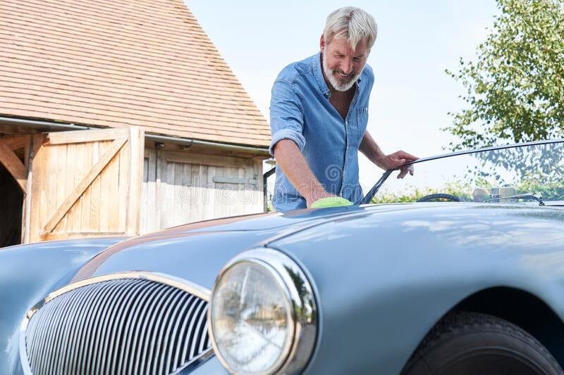 Mature Man Polishing Restored Classic Sports Car Outdoors At Home royalty free stock photos