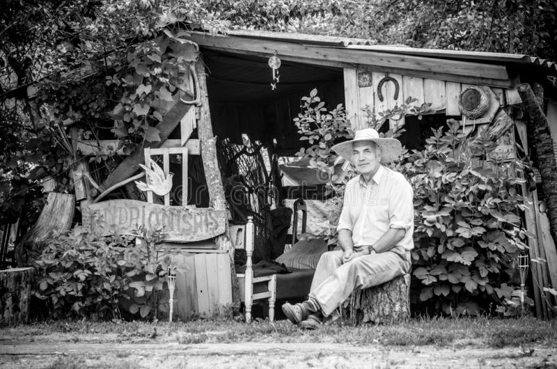 Mature man portrait, sitting near his outdoor shelter stock photography