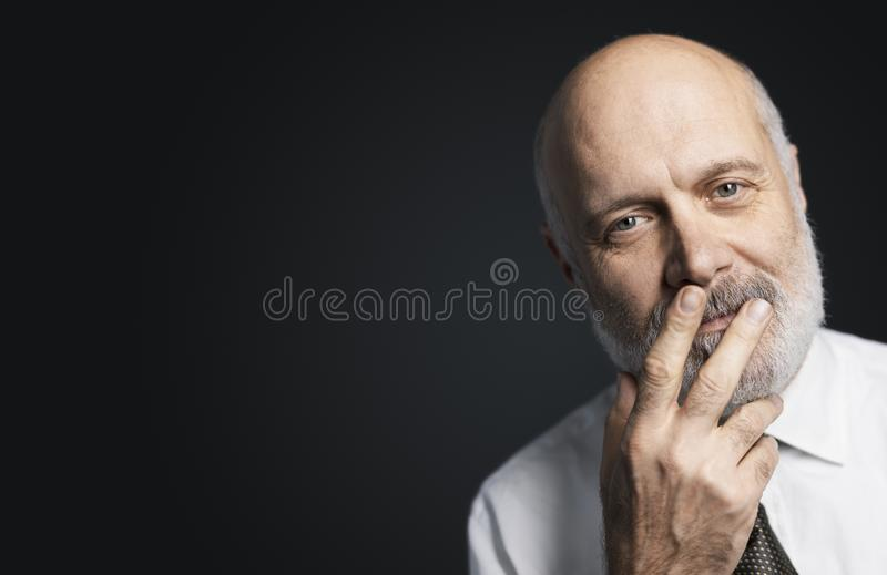 Mature man posing with a hand on his face royalty free stock photo