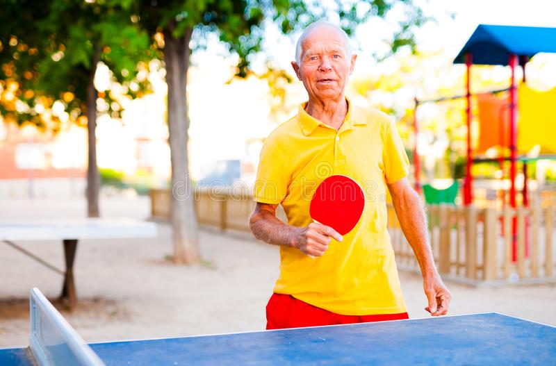 Mature man posing with rackets at table tennis. Happy mature man posing with rackets at table tennis stock photos