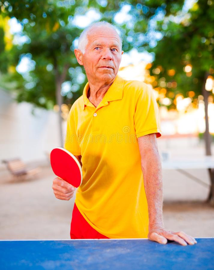 Mature man posing with rackets at table tennis. Happy mature man posing with rackets at table tennis royalty free stock photos