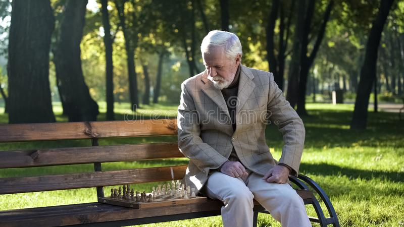 Mature man preparing chessboard for game sitting on bench in park, retirement. Stock photo royalty free stock image