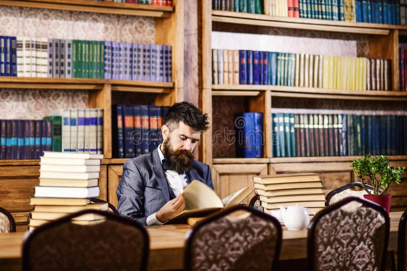 Mature man or professor with long beard and calm face. Historian sits in library and reads old books. Historical research, profession, intelligence concept royalty free stock photography