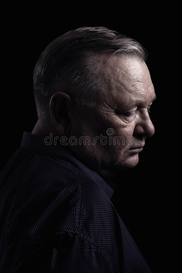 Mature man profile. Classic profile portrait of aged man with closed eyes wearing shirt against black background - retirement concept stock photography