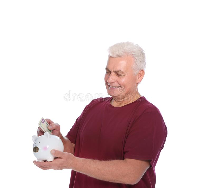 Mature man putting money into piggy bank. On white background royalty free stock photos