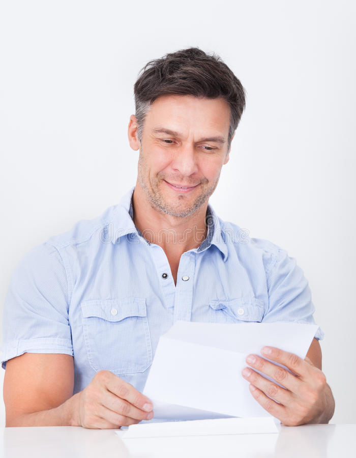 Mature man reading letter royalty free stock images