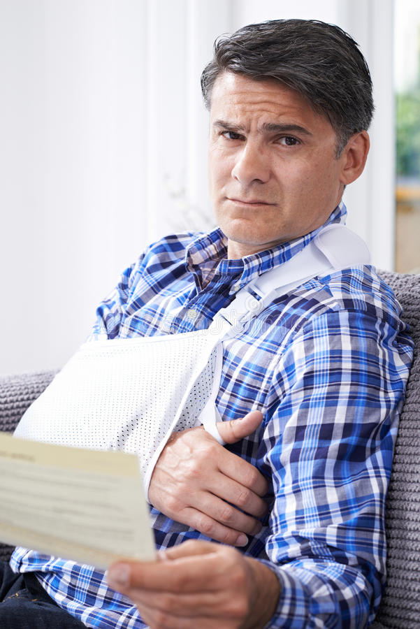Mature Man Reading Letter About Injury royalty free stock photo
