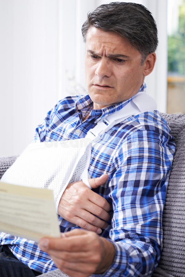 Mature Man Reading Letter About Injury stock image