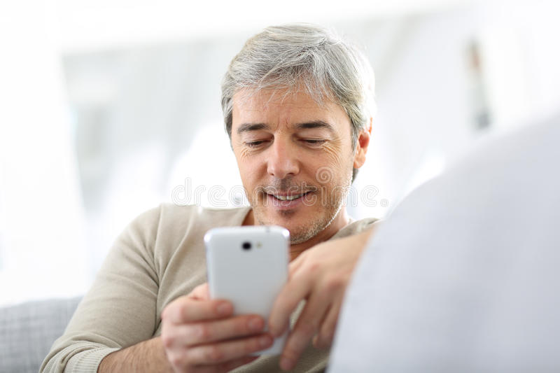 Mature man reading message on smartphone royalty free stock image