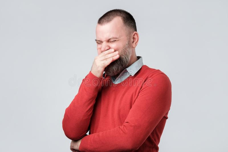 Mature man in red sweater laughs happily at funny joke, being in good mood royalty free stock photo