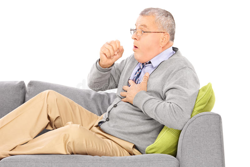 Mature man seated on a sofa coughing royalty free stock image